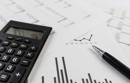 bookkeeping and accounting business concept, calculator and pen on data sheets and printed charts