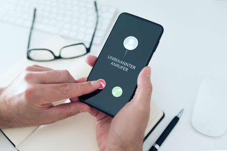 close-up view of person rejecting call from unknown number with text UNBEKANNTER ANRUFER, German for unknown caller, on smartphone, phone scam and phishing concept
