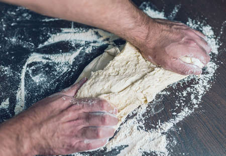 close-up of man kneading dough an wooden table, food preparation concept