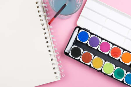 above view of watercolor paintbox, paint brush, sketchbook and glass of water on pink background, painting with watercolors and being creative concept
