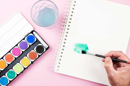 painting with watercolors, top view of paintbox, sketch pad and person using paintbrush Stock fotó