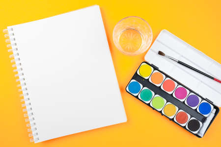 above view of watercolor paintbox, paint brush, sketchbook and glass of water on orange background, painting with watercolors and being creative concept Stock fotó