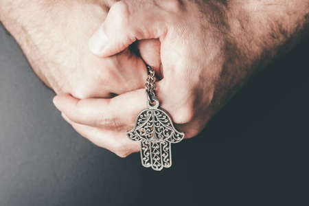 close-up of folded hands holding Hamsa amulet also known as Hand of Fatima used to protect against evil eye,, unluckiness, illness and bad fortune
