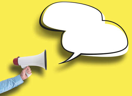 hand holding megaphone and speech bubble against yellow background, message template with copy space