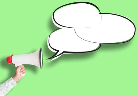 hand holding megaphone and speech bubble against green background, message template with copy space