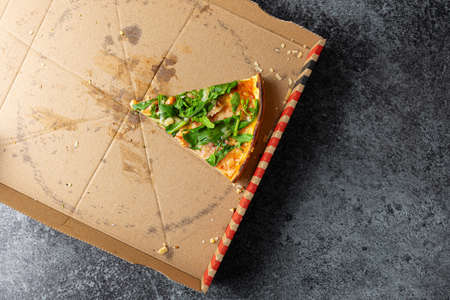 above view of last slice of pizza in cardboard box on stone kitchen counter