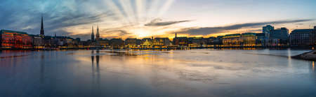 panoramic view of Alster Lake and cityscape in Hamburg, Germany during sunset against dramatic sky
