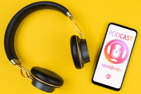 podcasting concept, above view of headphones and smartphone with podcast player mockup on yellow background Stock fotó