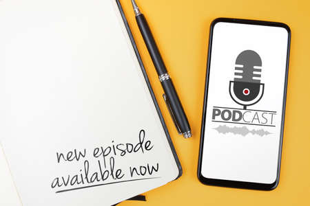 podcasting concept, text NEW EPISODE AVAILABLE NOW written on note pad and smartphone with podcast player mockup on orange desk