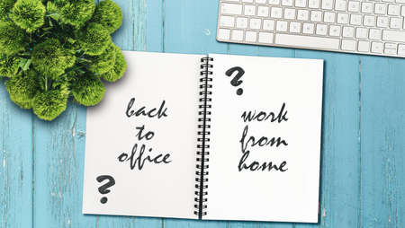 continue working from home or going back to the office concept with note pad and computer keyboard on rustic wooden table