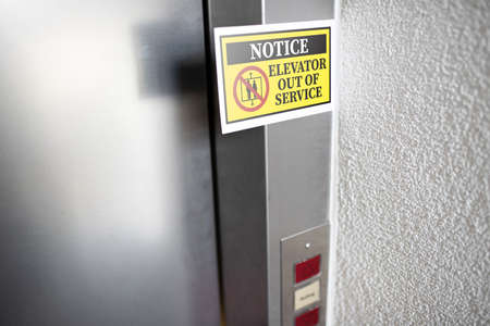yellow elevator out of service notice sign attached to elevator door, digital composite Stock fotó