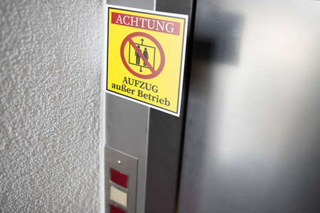 yellow service sign with German text for ELEVATOR OUT OF SERVICE attached to elevator door, digital composite Stock fotó