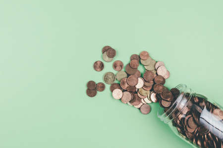 above view of small change Euro coins spilling out of glass jar on green background Stock fotó