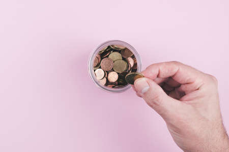 above view of hand putting coin in jar filled with small change Stock fotó