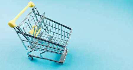 high angle view of miniature shopping cart on blue background