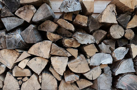 full-frame shot of stack of firewood, wood billets against wooden wall background