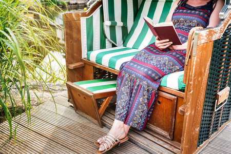 woman in summer dress relaxing in beach chair on deck or patio reading a book Banque d'images