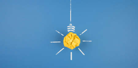 Light bulb made of crumpled-up yellow paper on blue Banque d'images