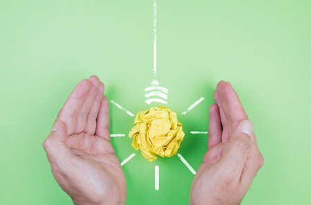 energy conservation and sustainability concept, hands shielding yellow paper light bulb on green background Banque d'images