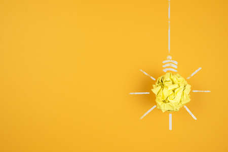 light bulb made of crumpled-up yellow paper on orange background, idea and innovation concept