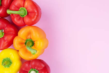 above view of bell peppers on pink colored background