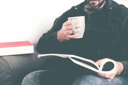 close-up of caucasian man reading magazine or journal on sofa while holding a cup of coffee