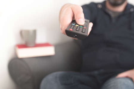 front view of person sitting on sofa using TV remote control to change channels Banque d'images