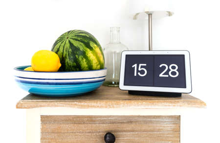 2020-08-31 Hamburg, Germany: Google Nest Hub smart display and smart speaker on kitchen shelf with water melon and lemons in fruit bowl