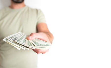 front view midsection of caucasian man offering or handing over money to someone else against white background