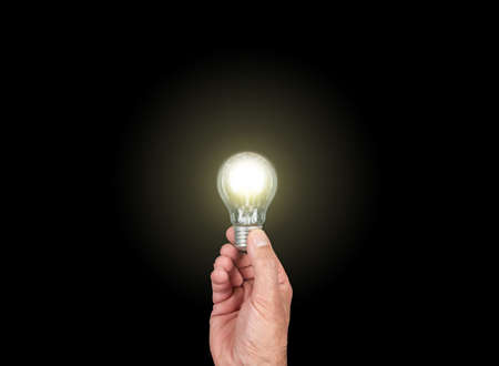 hand holding glowing light bulb against black background, having an idea concept