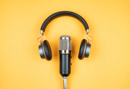podcasting concept, directly above view of headphones and recording microphone on orange background