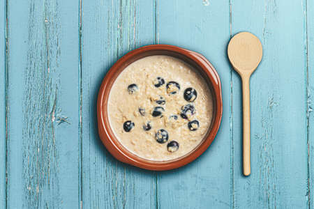 above view of healthy oatmeal or porridge with blueberries in bowl rustic blue wooden table 写真素材