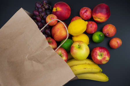 different fresh organic fruits in paper shopping back on black table background, healthy eating concept