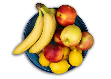 above view of fruit bowl with fresh organic bananas, apples, nectarines and lemons