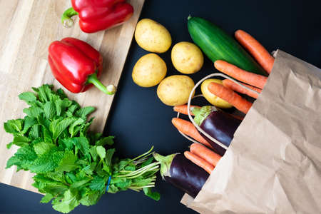 fresh organic vegetables spilling out of paper shopping bag on dark kitchen counter with wooden cutting board, healthy eating and cooking concept 写真素材
