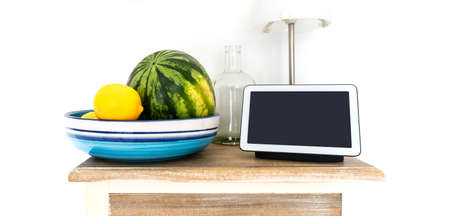 smart display and smart speaker on kitchen shelf with water melon and lemons in fruit bowl