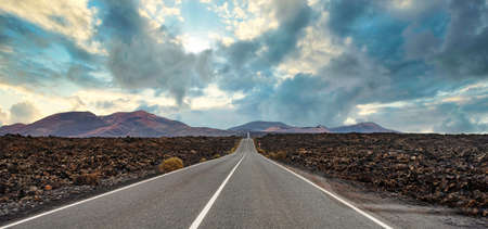 panoramic view of long straight empty road through volcanic landscape on Lanzarote, Canary Islands