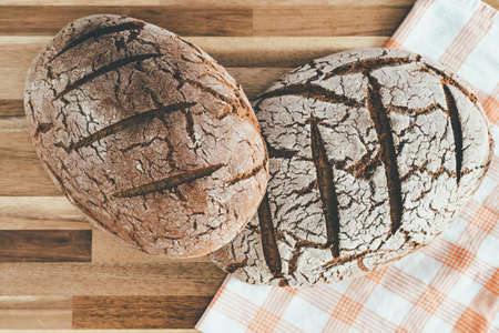 directly above view of two loaves of pure rye sourdough bread on wooden surface