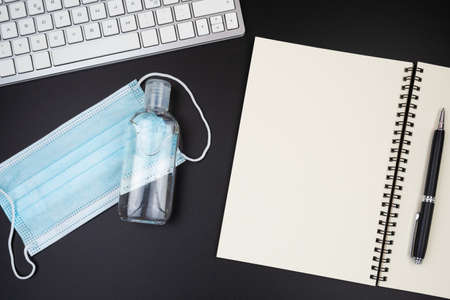 above view of disposable face mask and hand sanitizer on office desk 写真素材
