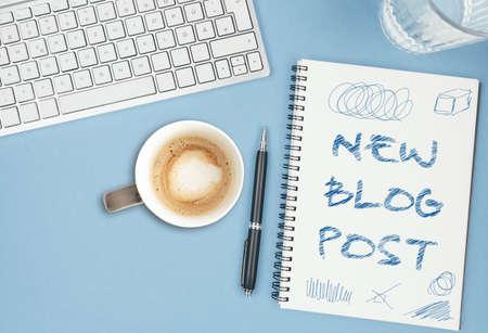 NEW BLOG POST scribbled on spiral notepad on blue desk with computer keyboard, blogging concept