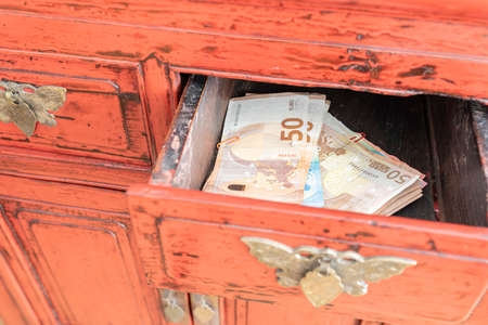 stacks of Euro bills in ajar drawer of antique cabinet, having lots of cash at home concept