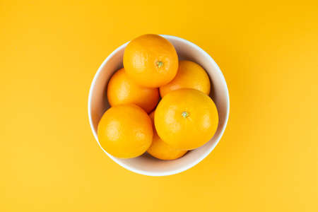 directly above view of white bowl filled with juicy oranges on orange colored background 免版税图像