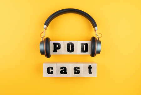 word PODCAST on wooden blocks and headphones on orange background, podcasting concept 免版税图像