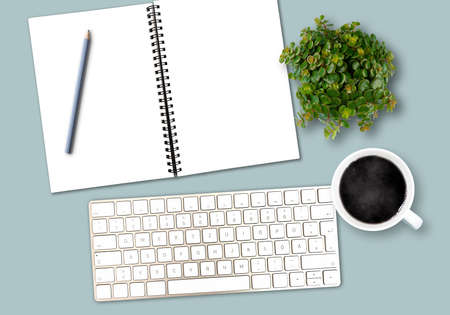 top view work desk template with computer keyboard, spiral notepad with copy space, pencil, coffee mug and potted plant