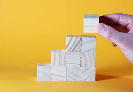 close-up of hand stacking wooden toy blocks in stairs shape against orange background, growth or ladder of success concept