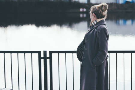 side view of heavily pregnant blonde woman looking at river