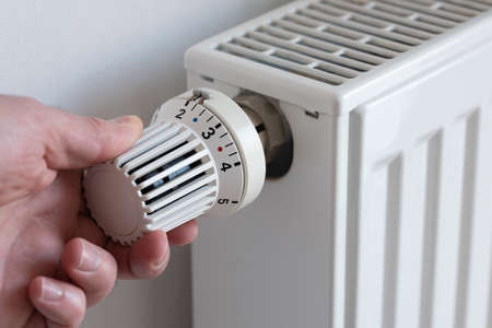close-up of person turning down thermostat on heater to save energy