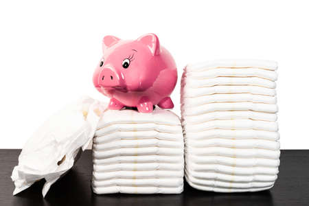 pink piggy bank on stack of disposable diapers against white background 免版税图像