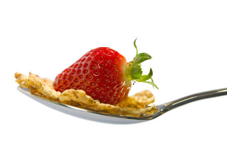 Strawberry on spoon with cereal flakes photo
