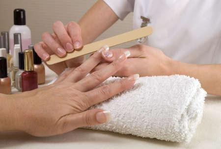 Manicurist filing clients nails